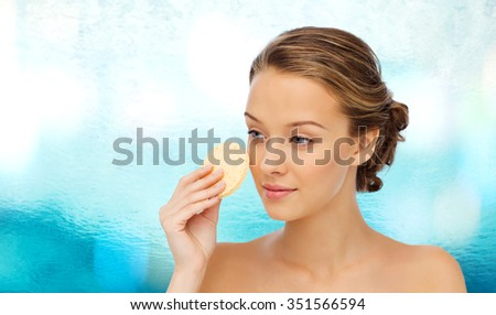 beauty, people and skincare concept - young woman cleaning face with exfoliating sponge over blue water background - stock photo