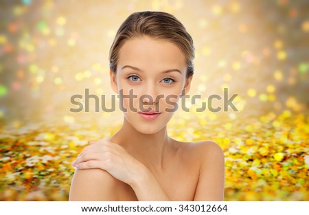 beauty, people, body care and health concept - smiling young woman face and hand on bare shoulder over golden holidays lights or yellow glitter background - stock photo