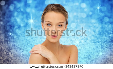 beauty, people, body care and health concept - smiling young woman face and hand on bare shoulder over blue holidays lights or glitter background - stock photo