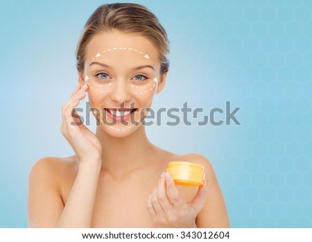 beauty, people, cosmetics, skincare and anti-aging concept - happy young woman applying cream to her face with white arrows over blue background - stock photo