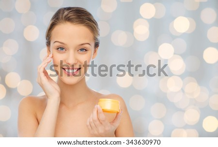 beauty, people, cosmetics, skincare and cosmetics concept - happy young woman applying cream to her face over holidays lights background - stock photo