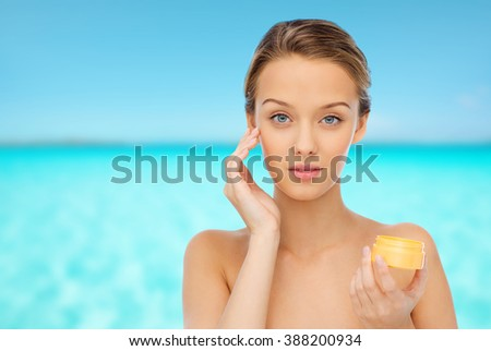 beauty, people, cosmetics, skincare and cosmetics concept - young woman applying cream to her face - stock photo