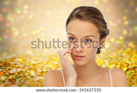 beauty, people, cosmetics, skincare and health concept - young woman applying cream to her face over golden holidays lights or yellow glitter background - stock photo