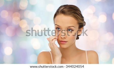 beauty, people, cosmetics, skincare and health concept - young woman applying cream to her face over purple holidays lights background - stock photo