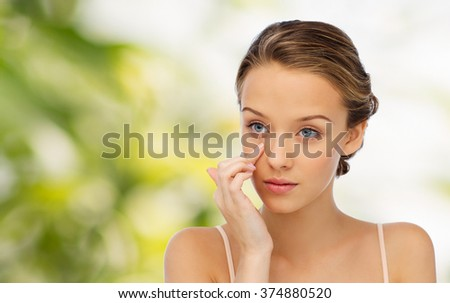 beauty, people, cosmetics, skincare and health concept - young woman applying cream to her face over green natural background - stock photo