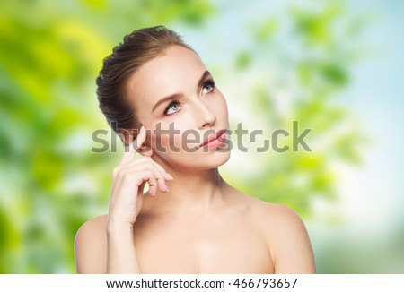 beauty, people, eco and health concept - beautiful young woman touching her face over green natural background