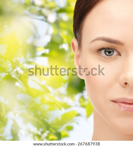 beauty, people, ecology, organic and health concept - beautiful young woman face over green leaves background - stock photo