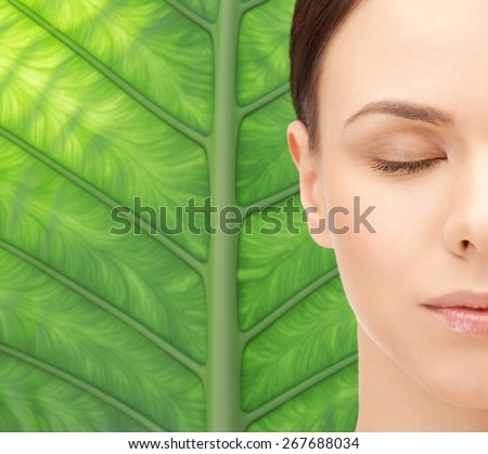 beauty, people, ecology, organic and health concept - beautiful young woman face over green palm tree leaf background - stock photo