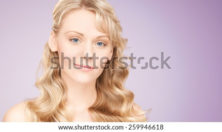 beauty, people, hair care and health concept - beautiful young woman face with long wavy hair over violet background - stock photo