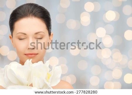 beauty, people, holidays and health concept - beautiful young woman smelling flowers with closed eyes over lights background - stock photo