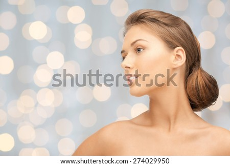beauty, people, holidays, luxury and health concept - beautiful young woman face looking aside over lights background - stock photo