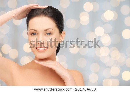 beauty, people, holidays, luxury and health concept - beautiful young woman touching her face and chin over lights background - stock photo