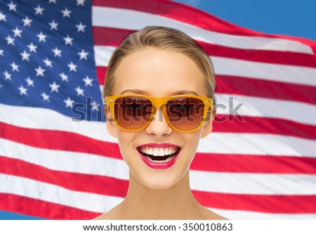 beauty, people, nationality and patriotism concept - smiling young woman in sunglasses with pink lipstick on lips over american flag background
