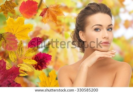 beauty, people, season and health concept - beautiful young woman touching her face over autumn leaves background - stock photo