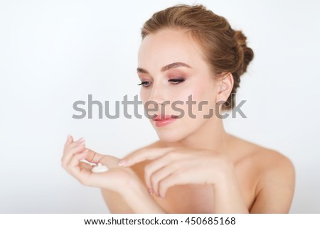 beauty, people, skincare and cosmetics concept - happy young woman with moisturizing cream on hand - stock photo