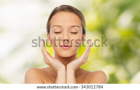 beauty, people, skincare and health concept - young woman face and hands over green natural background - stock photo