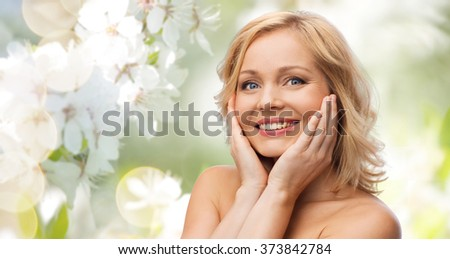 beauty, people, skincare and natural cosmetics concept - smiling woman with bare shoulders touching face over cherry blossom background - stock photo