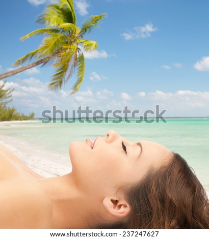 beauty, people, travel and health concept - beautiful young woman lying with closed eyes over tropical beach background