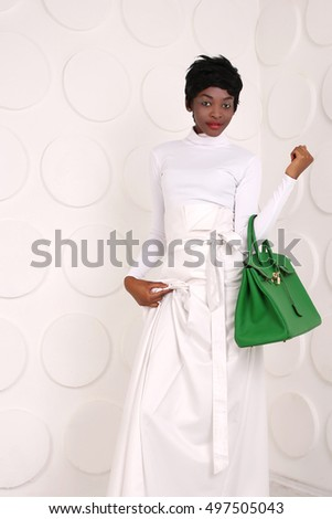 Beauty photo of young elegant african american woman. Girl wearing white clothes, green handbag. stylish evening dress African woman. Looking at camera. Glamour makeup. Fashion photo.