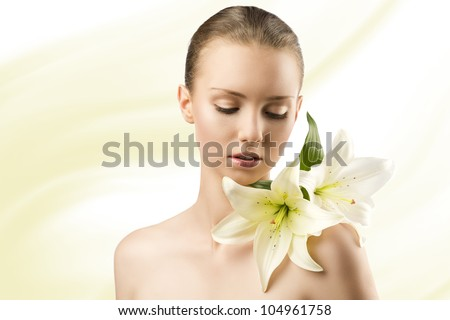 beauty portait of pretty young girl with lilies, she is slightly turned of three quarters at left and looks lilies on her left shoulder