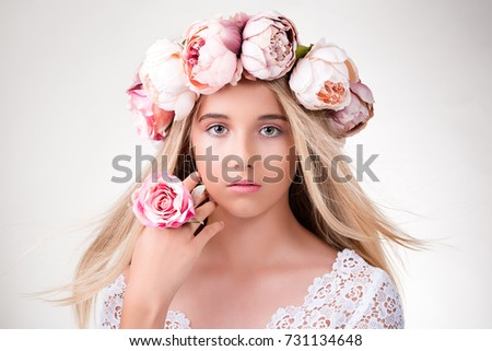 Beauty portrait. Beautiful blonde girl with wreath of flowers. Looking at camera. Youth, happiness concept