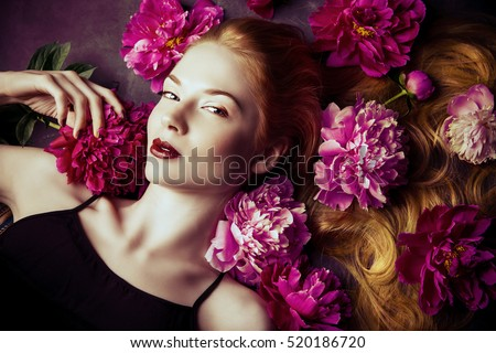 Beauty portrait. Beautiful blonde woman with sensual maroon lips lying among peony flowers. Cosmetics, make-up. Perfumery.