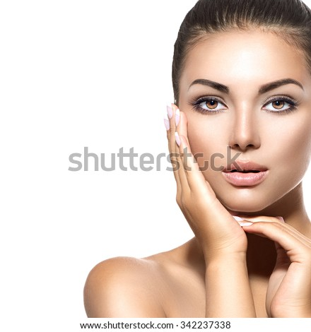 Beauty Portrait. Beautiful Spa Brunette Woman Touching her Face. Perfect Fresh Skin. Pure Beauty Model Girl. Youth and Skin Care Concept. Isolated on a white background