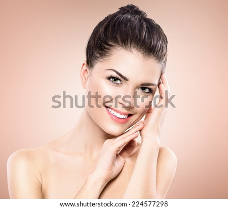 Beauty Portrait. Beautiful Spa Girl Touching her Face. Perfect Fresh Skin. Pure Beauty Model Girl. Youth and Skin Care Concept. Beauty Teenage Model Girl Portrait over pink background - stock photo