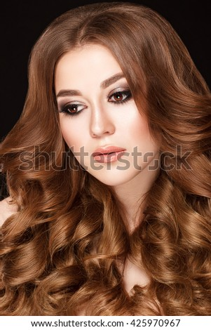 Beauty portrait. Beautiful woman with long dark blond hair on black background. Curly hair style and beautiful makeup.