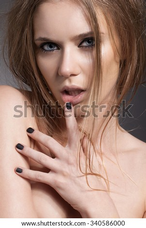 Beauty portrait closeup of a young attractive charming sensual woman with dark hair, perfect shiny clean skin, nude daily fresh makeup and blue eyes, black nails, looking at camera. - stock photo