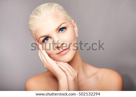 Beauty portrait face of beautiful blond woman with blue eyes and smooth skin, aesthetics skincare concept.