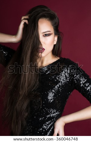 Beauty portrait of a beautiful feminine Asian brunette  with long hair in a black sequined dress with red lips in a dance in a studio on a red background holding hands at head - stock photo