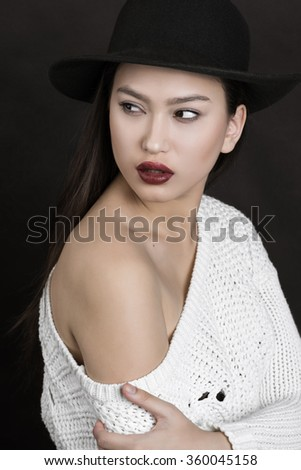Beauty portrait of a beautiful feminine Asian brunette  with long hair in a green hat in a studio on a background in a white sweater with bared shoulders - stock photo