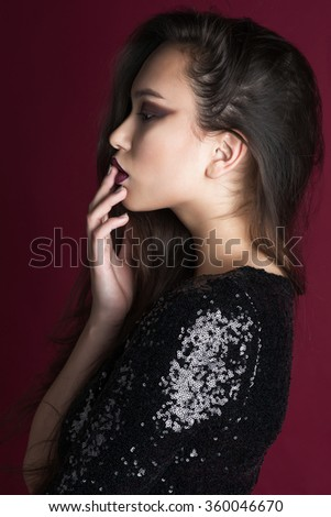 Beauty portrait of a beautiful feminine Asian brunette  with long hair in a studio on a red background in a black sequined dress with red lips standing sideways holding hands lips - stock photo