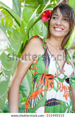 Beauty portrait of a beautiful young woman standing with lush forest tropical leaves in an exotic travel destination, smiling with a red hibiscus flower in her hair, outdoors.