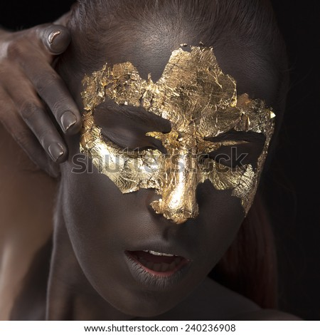 Beauty portrait of a brown-skinned girl with golden makeup of foil