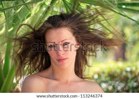 Beauty portrait of a brunette woman over palmtree background - stock photo