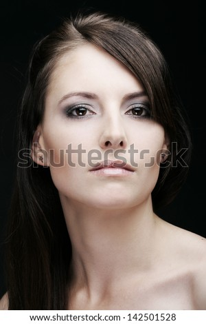 Beauty portrait of a caucasian woman with long brown hair looking at camera with a serious expression and intense look in her eyes, on a black background - stock photo