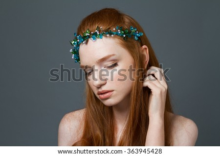 Beauty portrait of a charming redhead woman with hoop on her head posing over gray background - stock photo