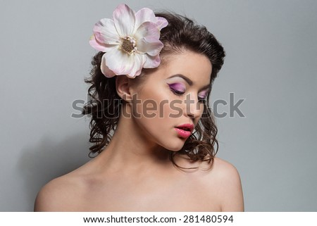 Beauty portrait of a girl with a flower in her hair. Beautiful young brunette