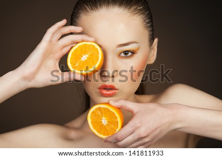 Beauty portrait of a girl with orange on a brown background