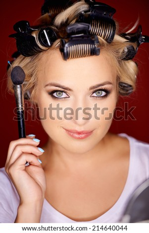 Beauty portrait of a gorgeous young blond woman with her hair in curlers wearing eye makeup holding up a cosmetics brush in her hand - stock photo