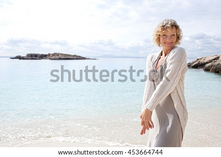 Beauty portrait of a healthy senior woman in a tranquil beach destination playful on shore, smiling and looking at the camera on holiday, outdoors. Mature female travel lifestyle, sunny exterior. - stock photo