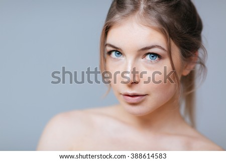 Beauty portrait of a lovely woman with fresh skin standing over gray background