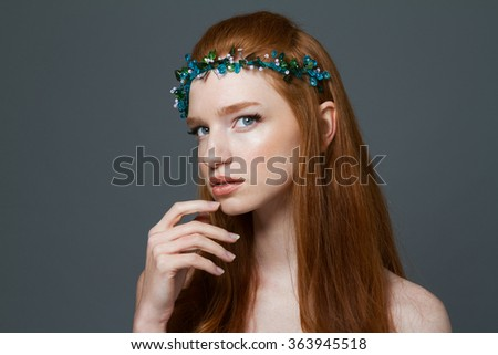 Beauty portrait of a pretty redhead woman with hoop on her head looking at camera over gray background - stock photo