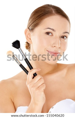 Beauty portrait of a pretty young woman with a lovely gentle smile holding two large bristle cosmetic brushes in her hand  isolated on white