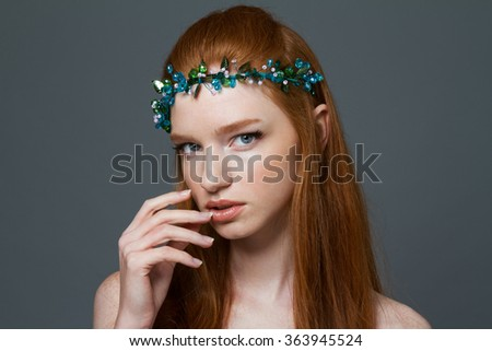 Beauty portrait of a redhead woman with hoop on her head looking at camera over gray background - stock photo