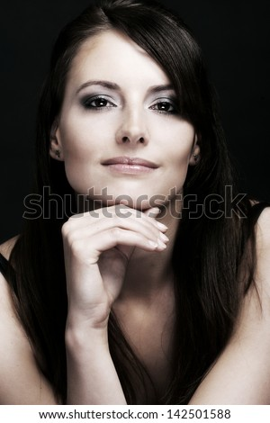 Beauty portrait of a smiling caucasian woman with long brown hairs, intense look in her eyes and resting her chin in the hand, looking at the camera on a black background - stock photo