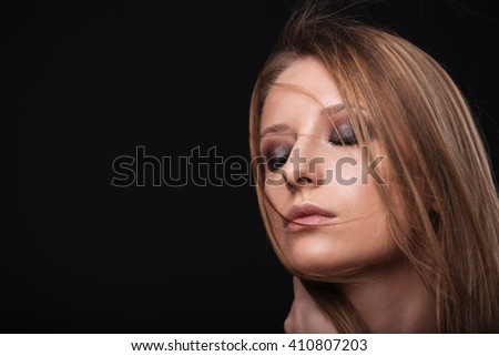 Beauty portrait of a woman with fresh skin and closed eyes over black background