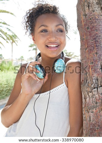 Beauty portrait of a young African American black adolescent girl joyful smiling by the beach on holiday with headphones on a sunny day, outdoors. Teenager travel technology lifestyle, exterior. - stock photo